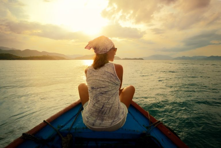 Girl sitting on a boat by the sunset